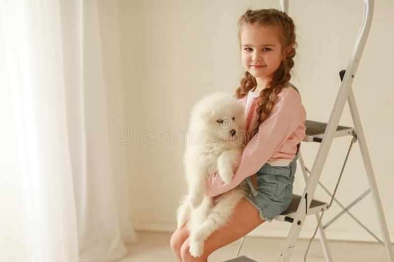 Baby Hugs the white fluffy puppy. Kids.  stock photo