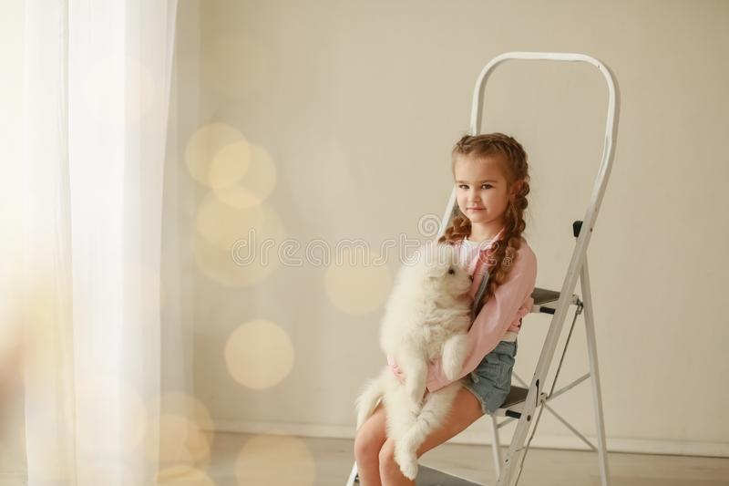 Baby Hugs the white fluffy puppy. Kids.  stock images