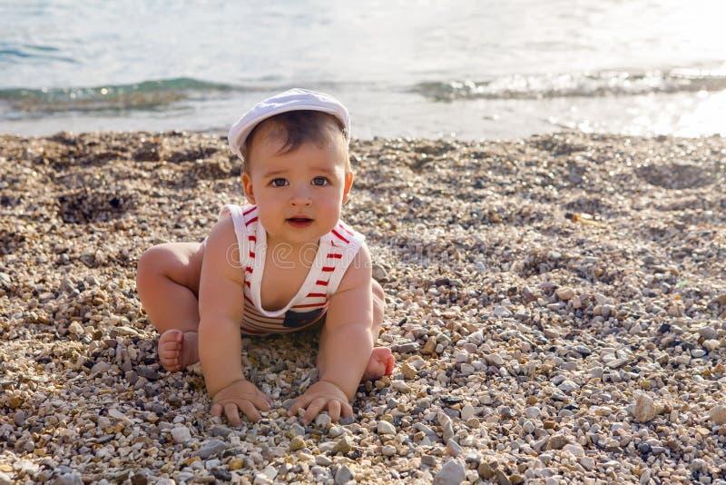 Baby im Hut auf Strandkieseln stockbilder