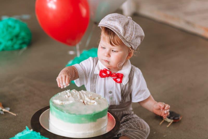Baby im Hut ersten Geburtstagskuchen essend Gl?ckliches junges M?dchen, das Taschen auf einem wei?en Hintergrund h?lt lizenzfreies stockfoto