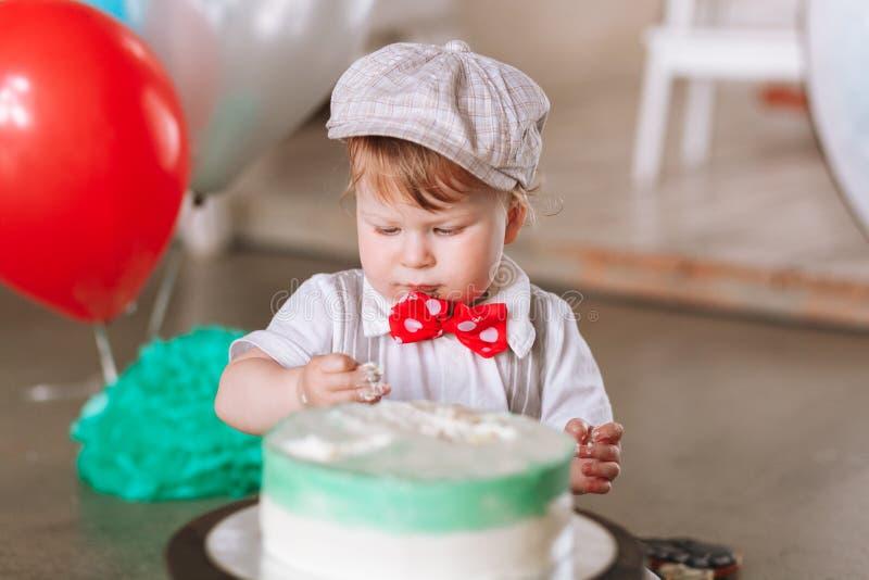 Baby im Hut ersten Geburtstagskuchen essend Gl?ckliches junges M?dchen, das Taschen auf einem wei?en Hintergrund h?lt stockfoto