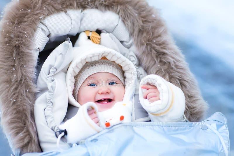 Baby im Spaziergänger in einem Winterpark stockfotos