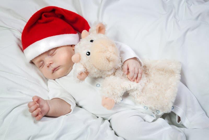 Baby im Weihnachtshutschlafenden umarmenden Lieblingsspielzeug lizenzfreie stockfotografie