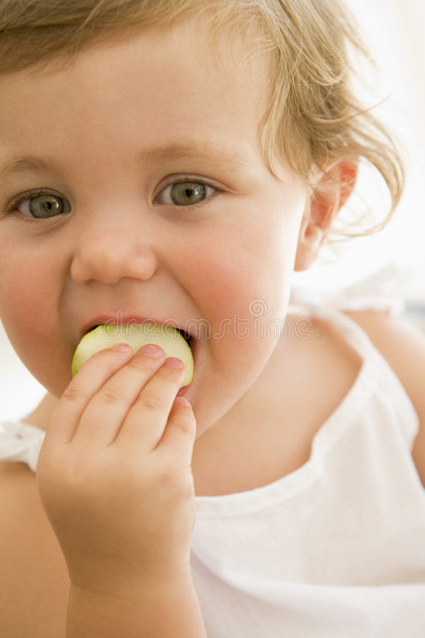 Baby indoors eating apple royalty free stock photography