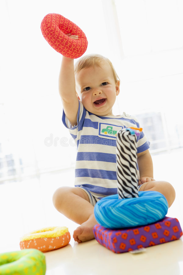 Baby indoors playing with soft toy royalty free stock photos
