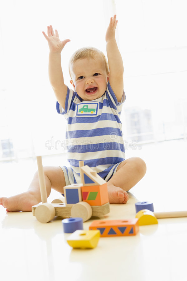 Baby indoors playing with truck royalty free stock image