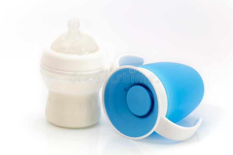 Baby infant no spill drinking cup and Baby bottle with milk. Trainer 360 degree drink bottle stock photos