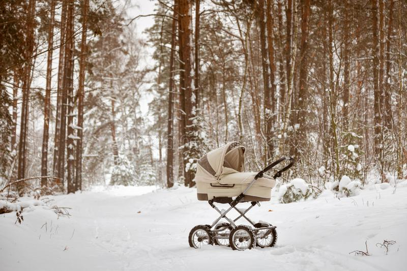 Baby infant stroller in snow in winter forest. Infant baby sleep inside the pram on fresh air.  royalty free stock photos