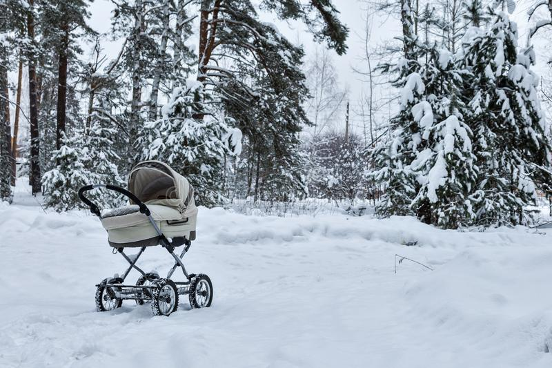 Baby infant stroller in snow in winter forest. It`s cold. Infant baby sleep inside the pram on fresh air. Baby infant stroller in snow in winter forest. Infant stock photography