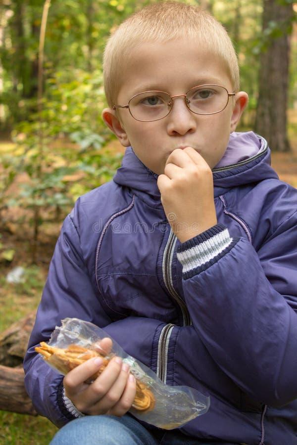 Baby isst im Fallwald, ein Schüler im Wald isst Käse stockbild