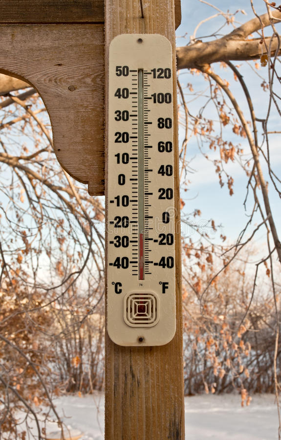 Baby, its cold outside. A thermometer is shown on the back porch of a residence in the middle of winter in the Rocky Mountains. The temperature shown is 15 royalty free stock photo