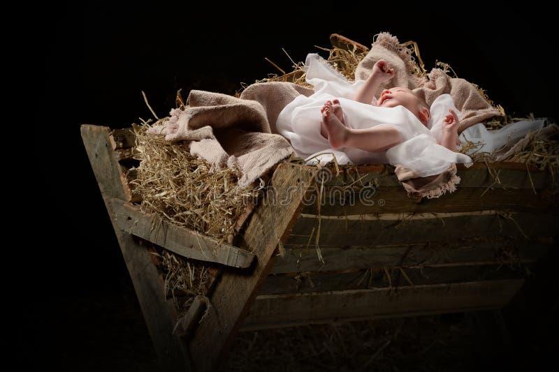 Baby Jesus auf einer Krippe stockfotos