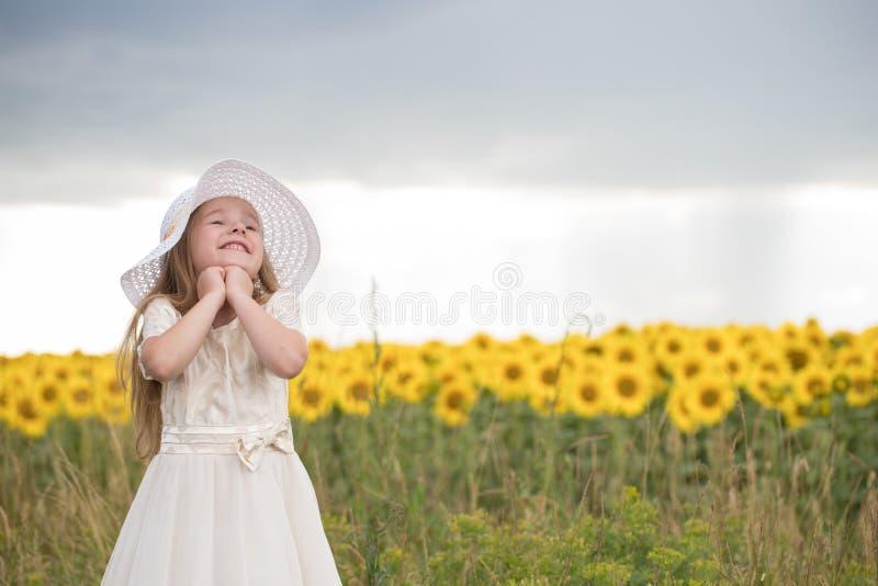Baby jublar för att le härlig flicka i en vit klänning och en vit hatt royaltyfria foton