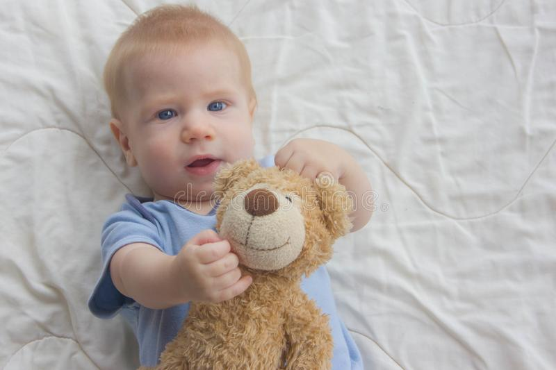 The baby with keeps a teddy bear. A toy in the hands of a baby royalty free stock images