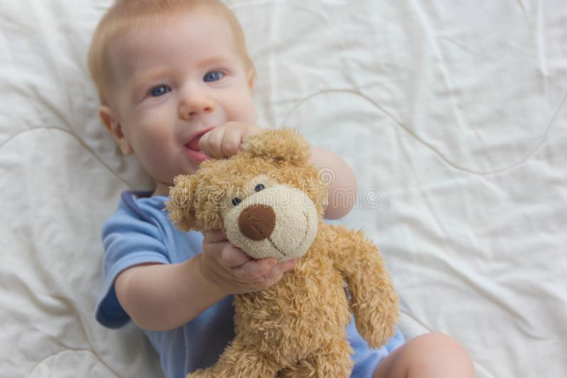The baby with keeps a teddy bear. A toy in the hands of a baby stock images