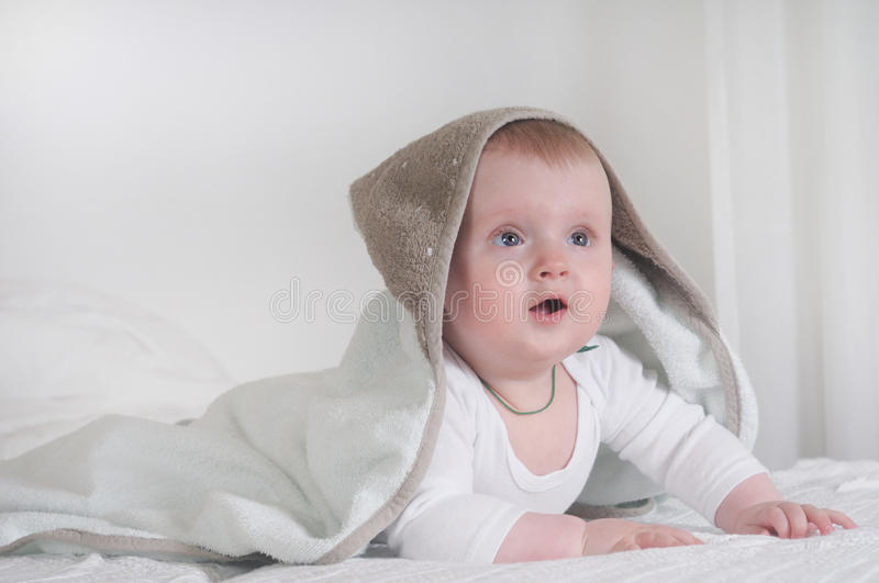 Baby kid under a hooded towel stock image