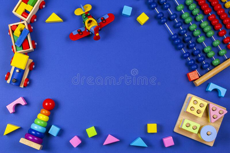 Baby kids toys background. Wooden educational geometric stacking blocks toy, wooden train, red airplane and colorful. Blocks on navy blue background. Top view stock image