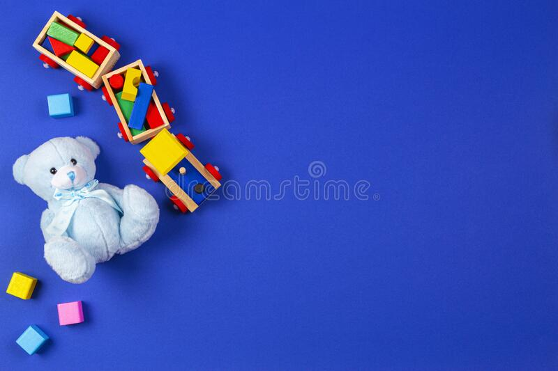 Baby kids toys background. Wooden train, blue teddy bear and colorful blocks on navy blue background.  stock photography