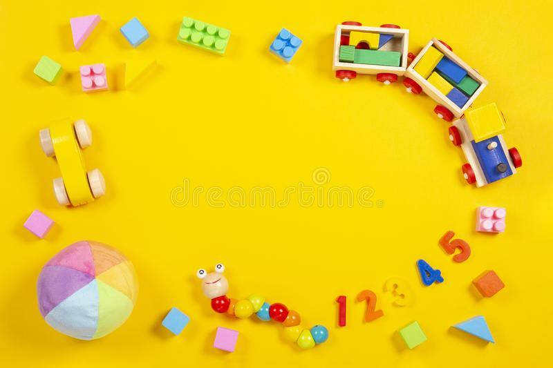 Baby kids toys background. Wooden train, car, colorful cubes and numbers on yellow background.  stock photography