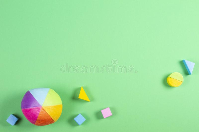 Baby kids toys frame with colorful ball and wooden bricks on green background.  royalty free stock image