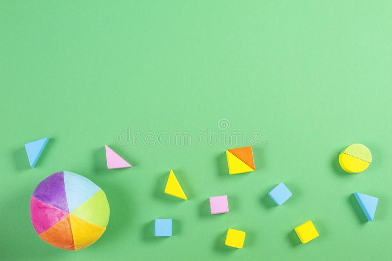 Baby kids toys frame with colorful ball and wooden bricks on green background.  royalty free stock photography