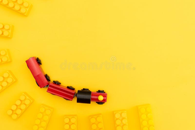 Baby kids toys frame with teddy bear, wooden toy car, colorful bricks on yellow background. Top view royalty free stock images
