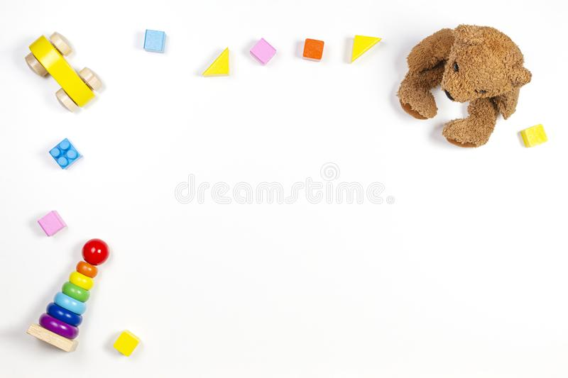 Baby kids toys frame on white background with teddy bear, wooden car, toy pyramid and colorful building blocks. Top view royalty free stock image