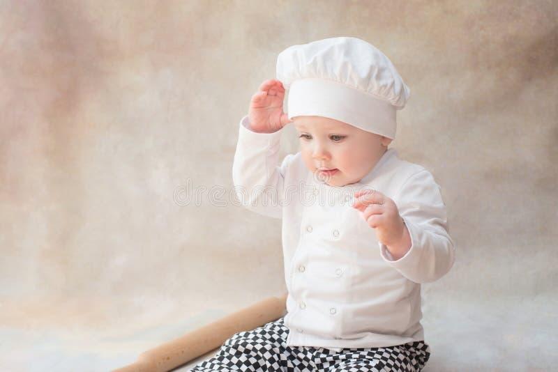 Baby, Kind im Chefkostümkoch innen lizenzfreie stockbilder