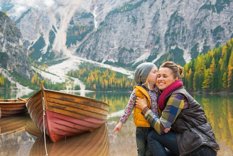 Baby kissing mother on lake braies in south tyrol royalty free stock photography