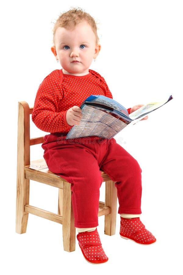 Baby kleidete im roten Sitzen auf Stuhlmesswert an stockfotografie