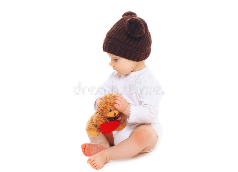 Baby in knitted brown hat with teddy bear toy sitting on white. Background royalty free stock images