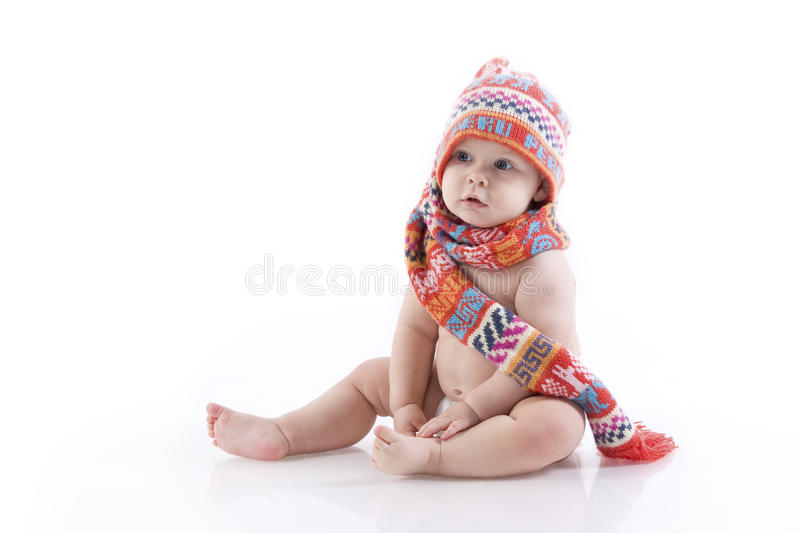 Baby in knitted hat and scarf. Baby in knitted hat, scarf and diaper sitting on the floor. On a white background with reflection royalty free stock photos