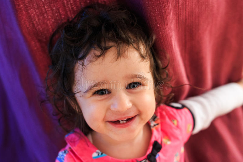 Baby krullend meisje die op een rode achtergrond glimlachen royalty-vrije stock foto's