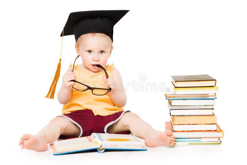 Baby las Buch im Staffelungs-Hut und in den Gläsern, das intelligente Kind, weiß stockbild