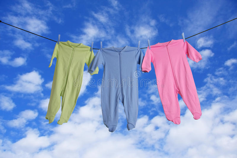 Baby laundry. Baby sleepers hanging on the clothesline stock image