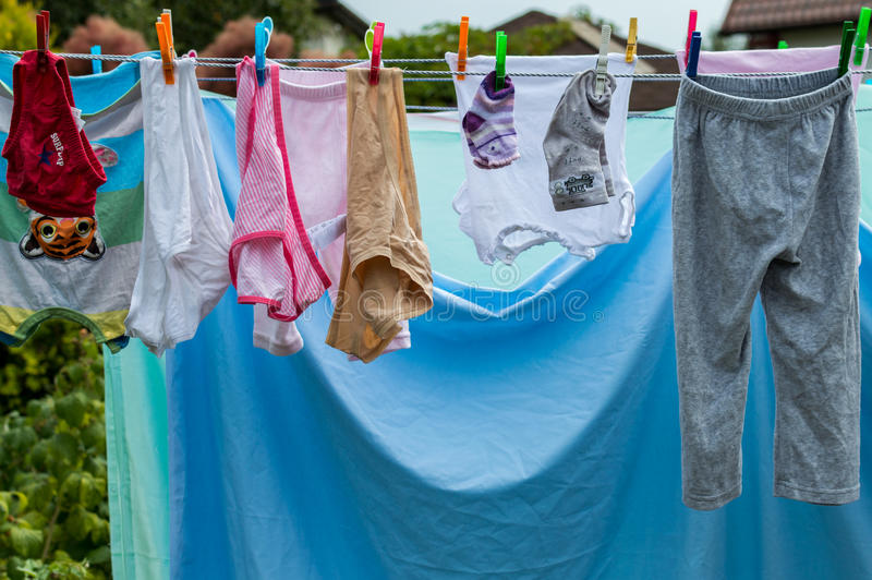 Baby laundry hanging on a clothesline in garden.  stock images