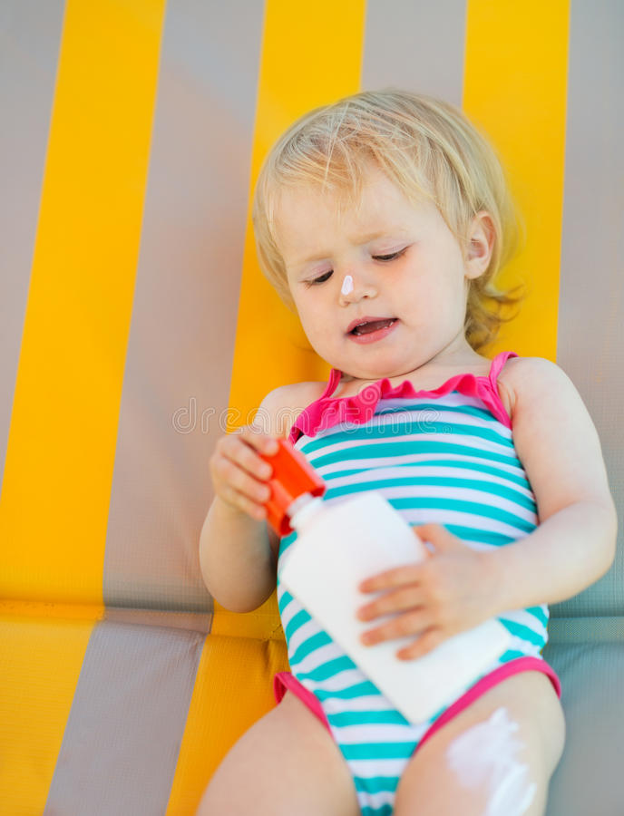 Download Baby Laying On Sun Bed With Sun Block Bottle Stock Image - Image: 25470711
