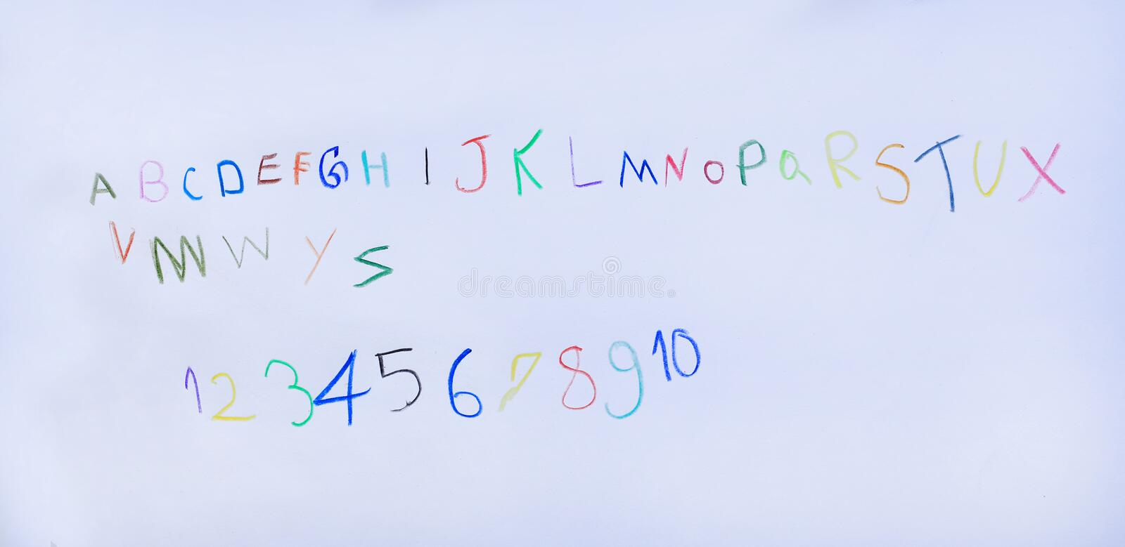 Baby learn to white with colored pencils for letters of alphabet and number on white paper royalty free stock photography