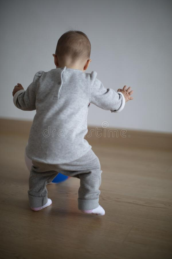 Baby learning how to walk on her first hunt for a ball. Baby girl making her first steps trying to get the ball balancing with hands royalty free stock images