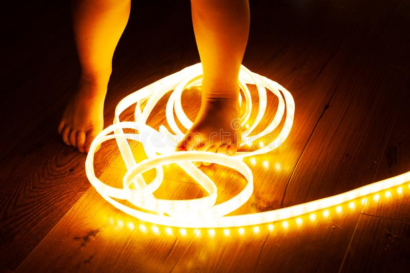 Baby legs, little girl stepping on LED strip, naughty baby playing with electricity, child safety concept and parental control. Close-up stock photo