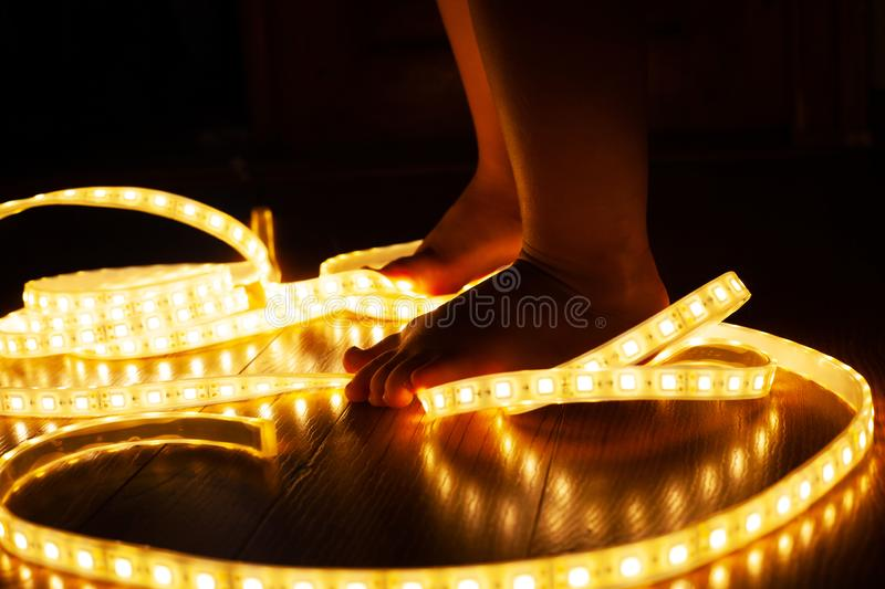 Baby legs, little girl stepping on LED strip, naughty baby playing with electricity, child safety concept and parental control. Close-up stock image