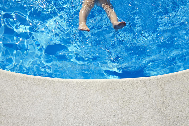 Baby legs in the swimming pool. At sunny day. Copy space stock image