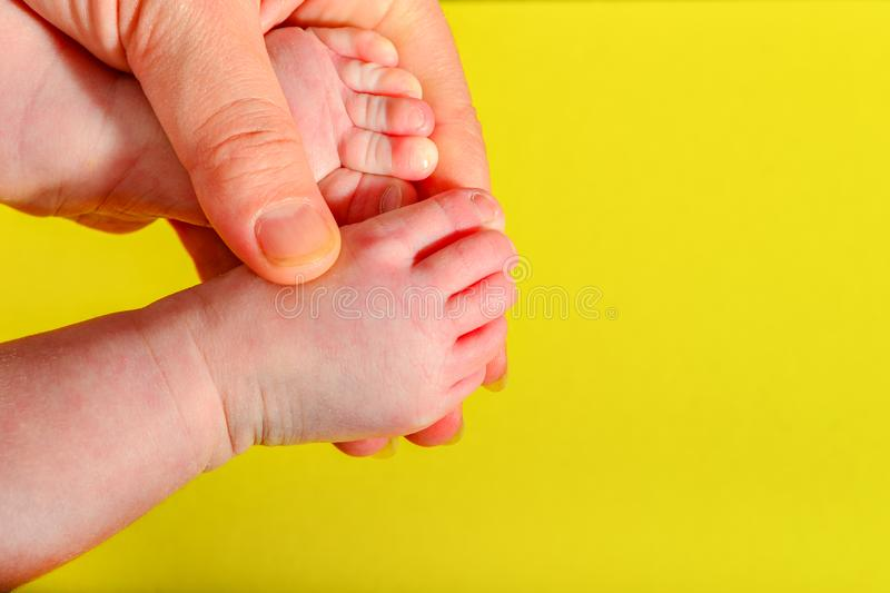 Baby legs on a yellow background, the mother holds the small legs of a newborn baby in her hand stock photo