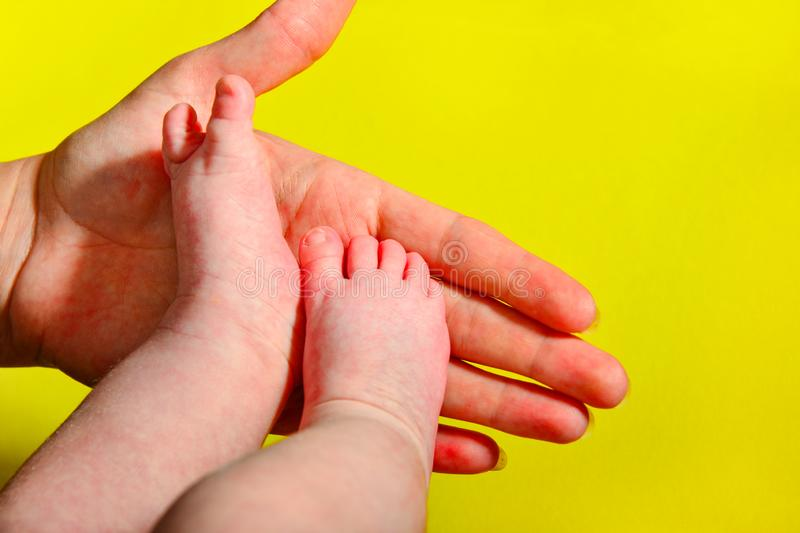 Baby legs on a yellow background, the mother holds the small legs of a newborn baby in her hand stock images