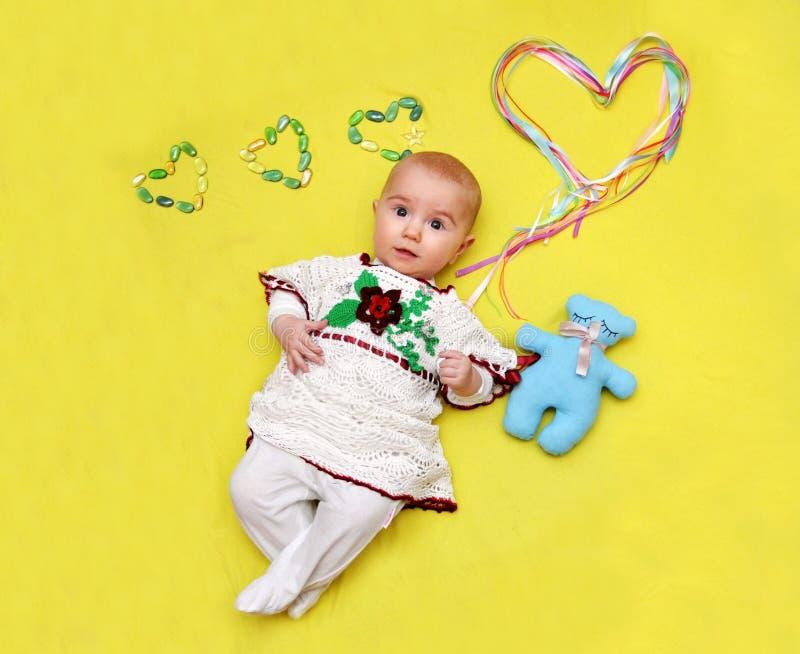 Baby liegt und hält ein großes Herz in seinen Händen, Liebe lizenzfreie stockfotos