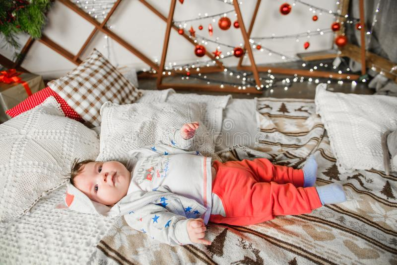 Baby lies on red and white christmas background. Photo of a healthy, chubby baby lying on its back, playing with toes, wearing a royalty free stock images