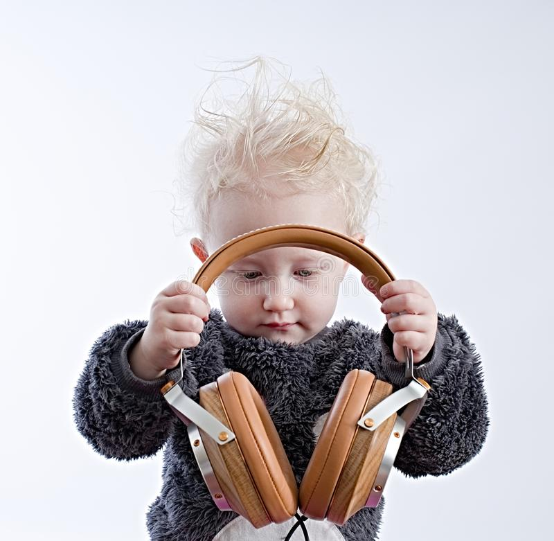 Baby listening music in headphones stock images