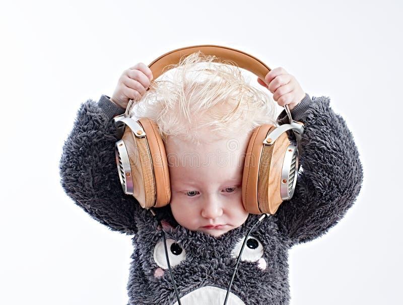Baby listening music in headphones royalty free stock image