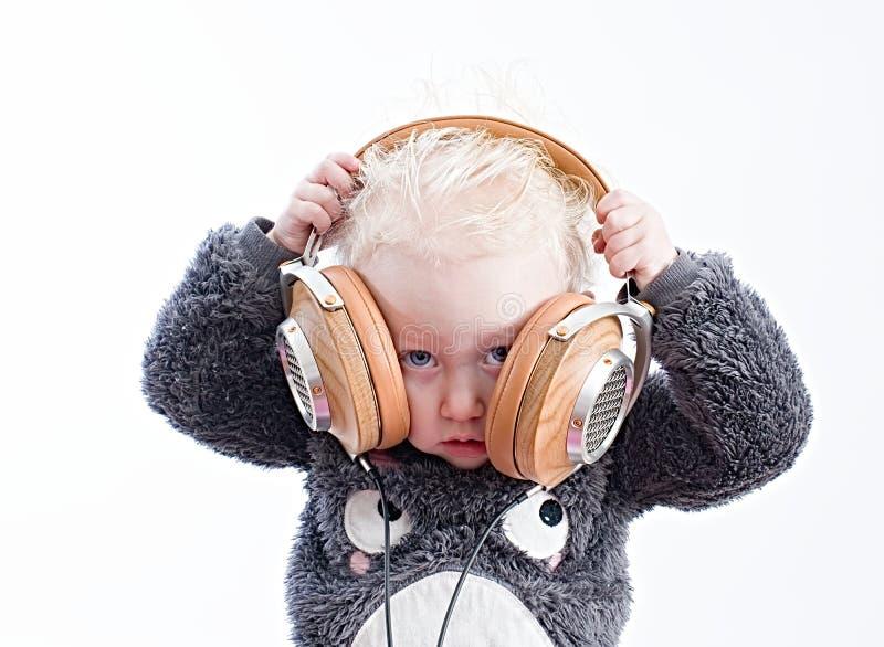Baby listening music in headphones stock photos