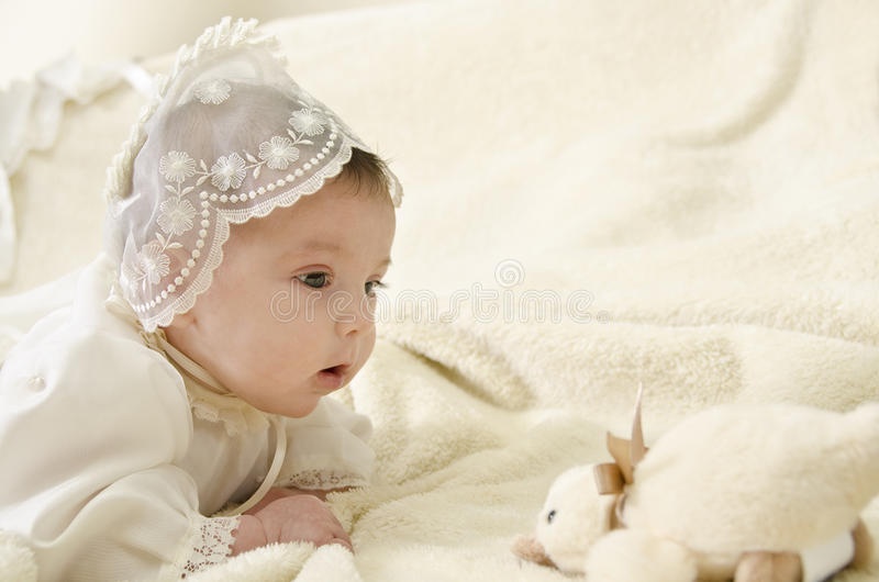 Baby llooking duck. Little baby with cereminial cap lying royalty free stock image